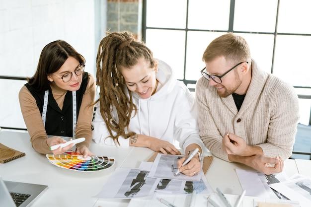 Gruppe junger kreativer designer von kleidung, die beim treffen über neue skizzen von models arbeitet