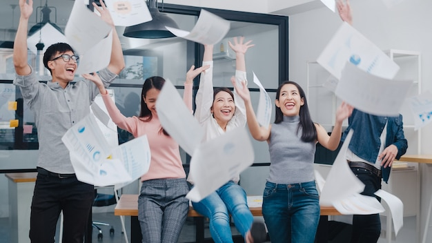 Gruppe junger kreativer leute aus asien in intelligenter freizeitkleidung feiern den projekterfolg und werfen dokumente im büro.