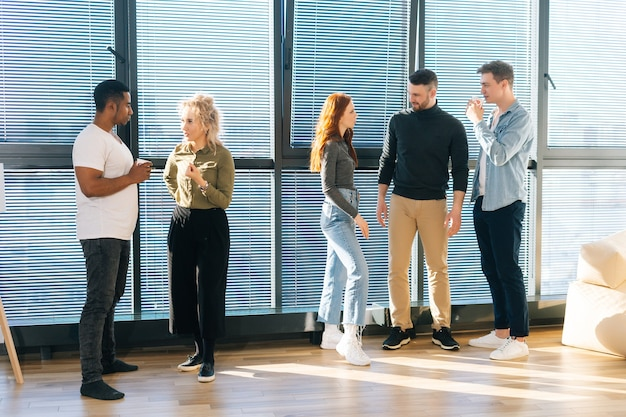 Gruppe junger kreativer multiethnischer mitarbeiter, die zeit miteinander im modernen büro verbringen, chatten und anstehende projekte besprechen. vorderansicht einer gruppe verschiedener kollegen, die in der arbeitspause sprechen.