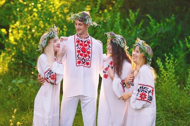 Gruppe junger leute auf slawischer traditioneller kleidung, die kupala nacht oder ivanа-kupala feiert