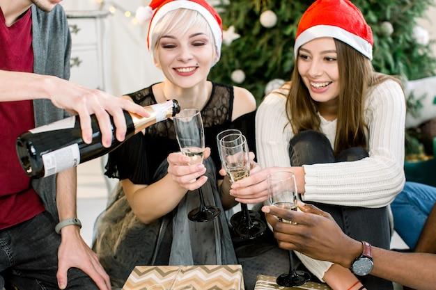 Gruppe junger leute, die am heiligabend mit gläsern anstoßen