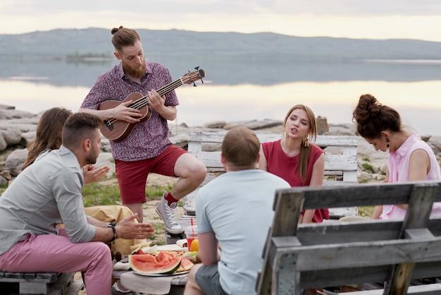 Gruppe junger leute, die am sommerabend um tisch nahe landschaftlich reizvollem see sitzen, essen, sprechen und gitarre spielen