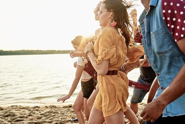 Gruppe junger leute, die am strand laufen