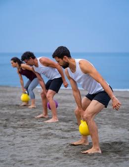 Gruppe junger leute, die am strand mit kesselglocken trainieren