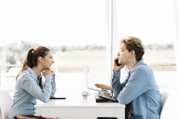 Gruppe junger leute, die an einem tisch mit einem mobiltelefon an einem tisch mit laptops sitzen