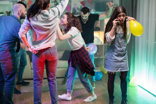 Gruppe junger leute, die auf einer party tanzen, während mädchen versucht, ein gespräch auf ihrem telefon zu führen.