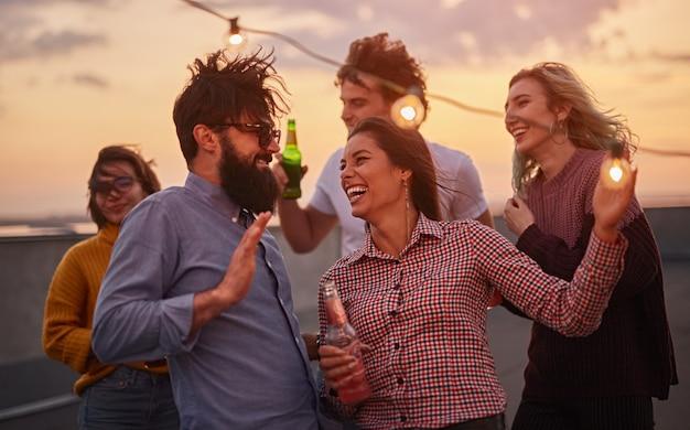 Gruppe junger leute, die bier trinken und zusammen auf dem dach entspannen
