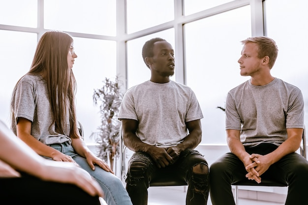 Gruppe junger leute, die den ideen ihres freundes zuhören. wirtschaft und bildung