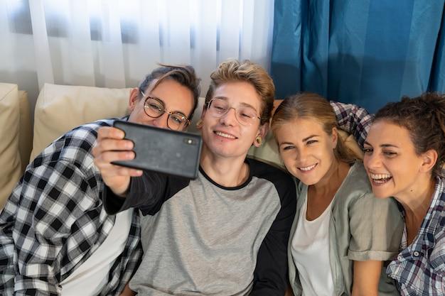 Gruppe junger leute, die ein selfie machen, das auf einem sofa sitzt