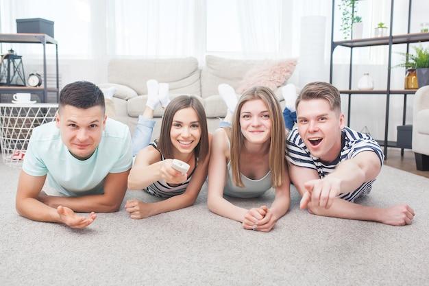 Gruppe junger leute, die fernsehen. emotionale freunde, die spaß haben und drinnen das spiel beobachten.