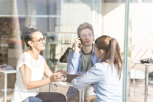 Gruppe junger leute, die ihr handy bei einem coworking benutzen