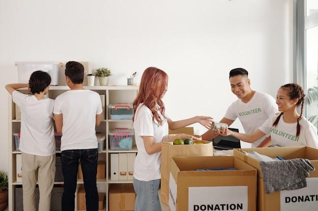 Gruppe junger leute, die im gemeindespendenzentrum arbeiten, kisten auspacken und lebensmittel und kleidung in regale stellen