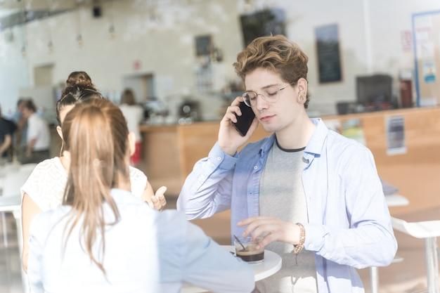 Gruppe junger leute, die kaffee trinken und ihr handy bei einem coworking benutzen