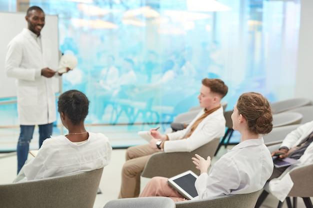 Gruppe junger leute, die laborkittel tragen und dem professor während des medizinischen seminars im coworking center zuhören, kopierraum