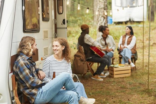 Gruppe junger leute, die sich im herbstlichen kopierraum mit dem wohnmobil im freien entspannen
