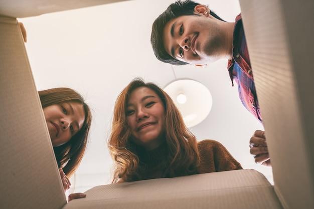 Gruppe junger leute, die sich öffnen und nach einem geschenk in der box suchen