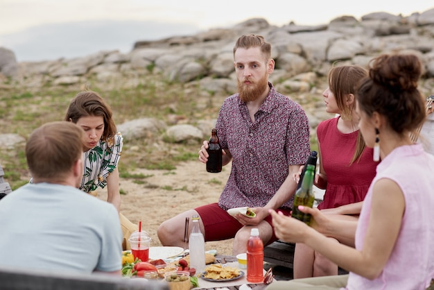 Gruppe junger leute, die sommerwochenende im freien verbringen, am tisch sitzen, essen, bier trinken und die neuesten nachrichten teilen