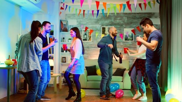 Gruppe junger leute, die zusammen auf einer party mit neonlichtern und guter musik tanzen. verrückte college-party