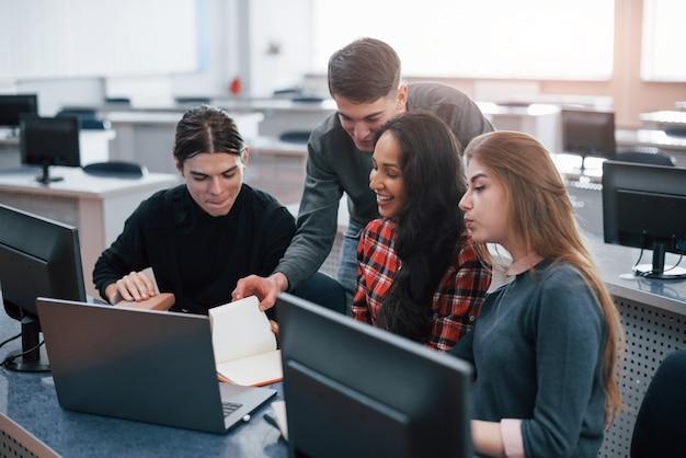 Gruppe junger leute in freizeitkleidung, die im modernen büro arbeiten