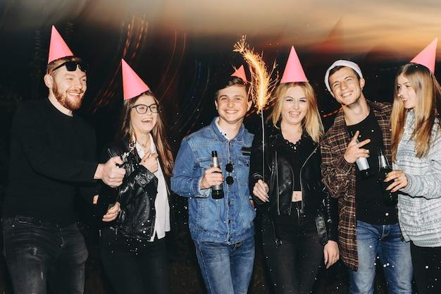 Gruppe junger leute mit flaschen alkohol und wunderkerzen, die lachen und kamera betrachten, während sie in der natur bei nacht stehen