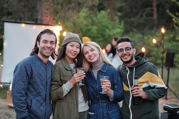 Gruppe junger liebevoller interkultureller freunde mit getränken, die in der reihe vor der kamera auf hintergrund der lichter und der grünen bäume stehen