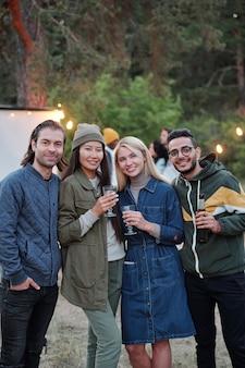 Gruppe junger liebevoller männer und frauen mit getränken, die lebensanlass feiern oder sich einfach gegen lichter und grüne bäume entspannen