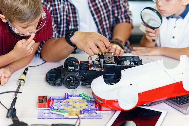 Gruppe junger männlicher schüler mit asiatischem wissenschaftler reparieren funkgesteuertes automodell.