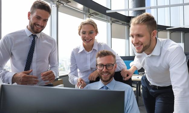 Gruppe junger moderner menschen in formeller kleidung mit modernen technologien bei der arbeit im kreativbüro.