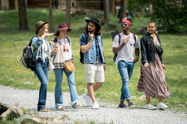 Gruppe junger multiethnischer freunde, die zusammen gehen und reden, während sie wochenenden auf dem festivalcampingplatz genießen