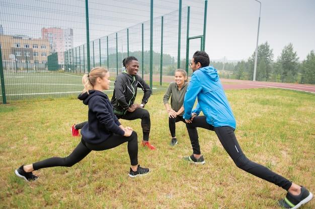 Gruppe junger multikultureller freundlicher leute, die streckübung für beine auf grünem gras in natürlicher umgebung tun