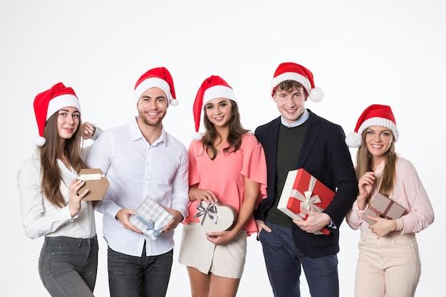 Gruppe junger schöner leute in den weihnachtsmützen mit geschenken freuen sich auf einem weißen hintergrund.