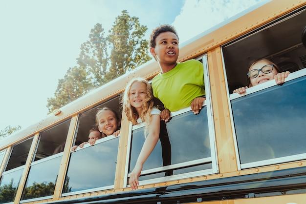 Gruppe junger schüler, die die grundschule in einem gelben schulbus besuchen - grundschulkinder, die spaß haben
