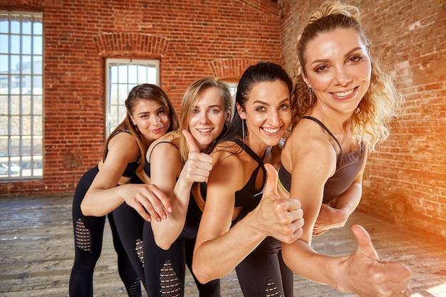 Gruppe junger sportmädchen, die sich nach einem training in einem geräumigen loftstudio ausruhen. weibliche freundschaft im fitnessstudio, entspannung nach fitness, drinnen, sonnenblendeffekt.