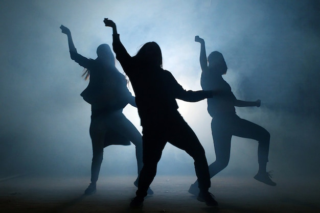 Gruppe junger tänzerinnen auf der straße bei nacht.
