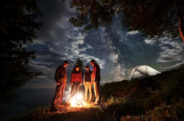 Gruppe junger touristen, die um das feuer nahe bäumen und zelten stehen