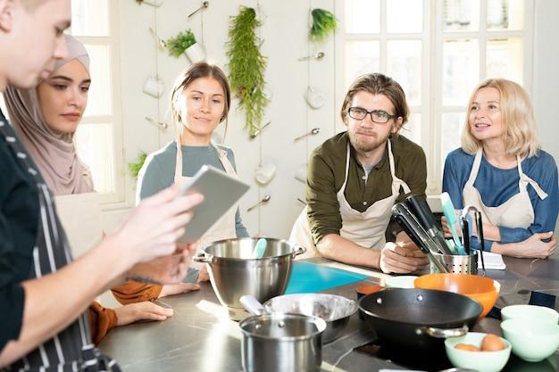 Gruppe junger und reifer menschen, die daran interessiert sind, zu kochen, den männlichen trainer mit digitalem tablet zu betrachten und ihm während der meisterklasse zuzuhören