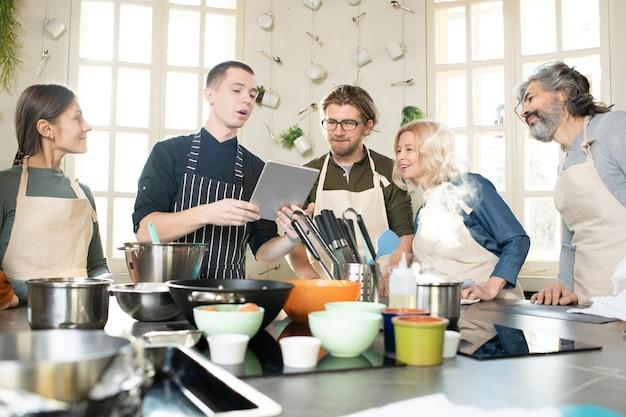 Gruppe junger und reifer menschen in schürzen, die auf den bildschirm des tablets schauen, der von einem männlichen kochtrainer gehalten wird, und ihm während der meisterklasse zuhören