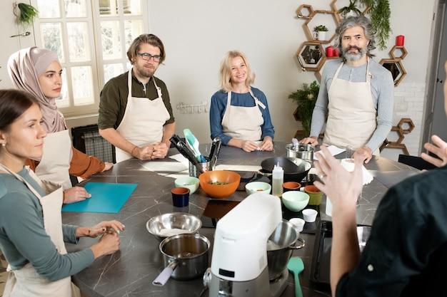 Gruppe junger und reifer menschen in schürzen, die einen männlichen kochtrainer betrachten und ihm während des meisterkurses in der küche zuhören