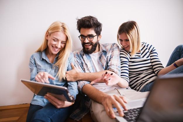 Gruppe junger verspielter mitarbeiter, die über internetinhalte von einem tablett lachen, während sie auf dem boden sitzen und sich an die wand lehnen.