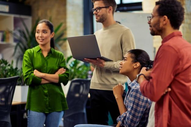 Gruppe junger, vielfältiger, multiethnischer geschäftsleute, die laptop verwenden und projektergebnisse diskutieren