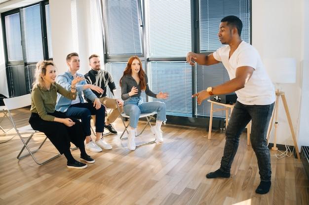 Gruppe junger, vielfältiger multiethnischer kollegen, die während des teambuildings in aktiven spielen spielen. fröhlicher afroamerikanischer mann, der scharaden mit freunden spielt, die zu hause pantomime zeigen.