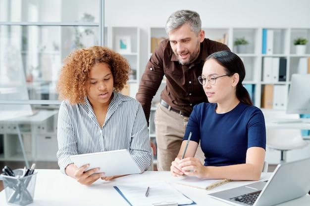 Gruppe junger zeitgenössischer selbstbewusster büroangestellter, die über präsentation vor konferenz während des sitzens im büro arbeiten