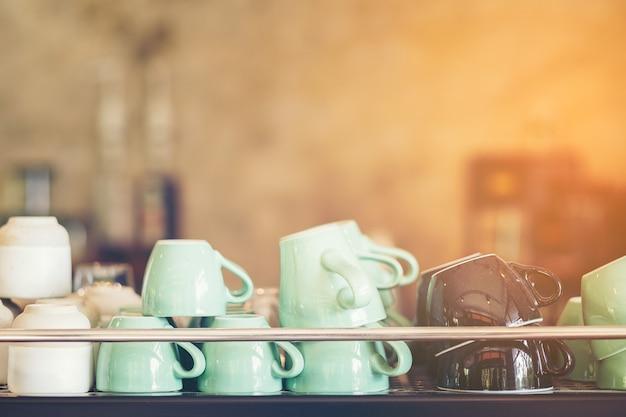 Gruppe kaffeetassen im cafébar-, grünbraun- und weißkaffeetassenglas auf regal im shop