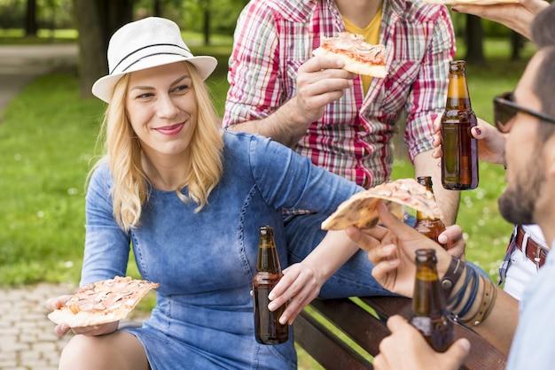 Gruppe kaukasischer freunde, die auf der bank sitzen und ihr bier im park genießen