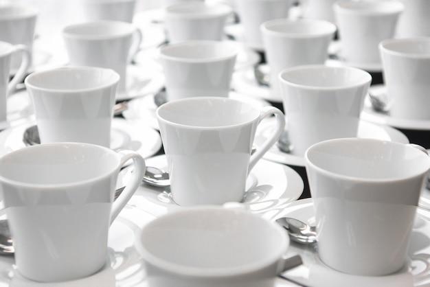 Gruppe keramischer weißer schale umhüllungstee oder -kaffee.