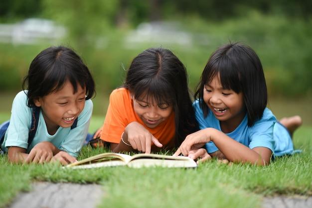 Gruppe kinder, die das lesen auf rasenfläche liegen