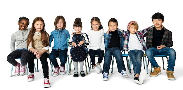 Gruppe kinder, die das zusammengehörigkeits-glück lächeln auf weißem blackground sitzen