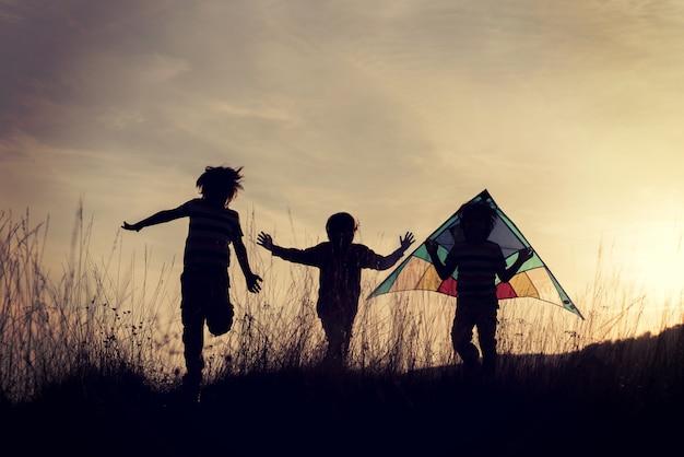 Gruppe kinder, die ihre zeit auf der wiese während des sonnenuntergangs genießen