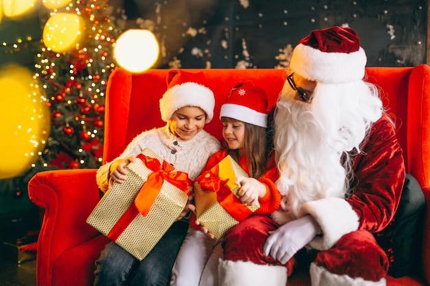 Gruppe kinder, die mit sankt und geschenken auf weihnachtsabend sitzen