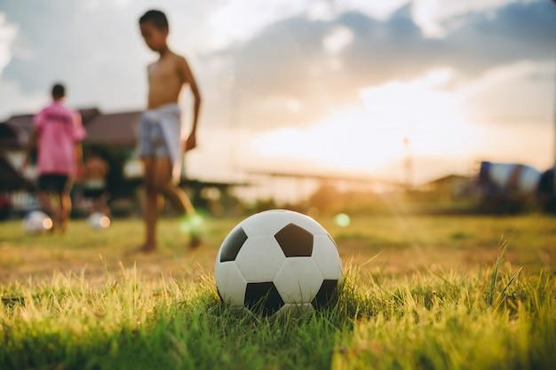 Gruppe kinder, die spaß haben, straßenfußballfußball für übung im ländlichen gebiet der gemeinschaft zu spielen